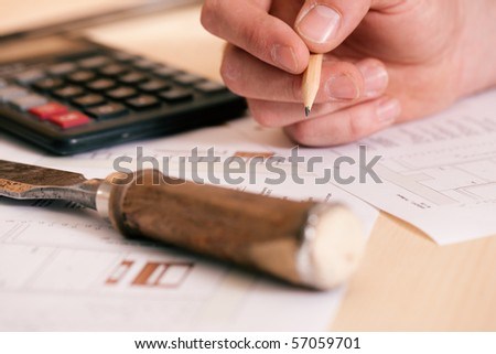 Carpenter planning his work - man (only hands to be seen) working with set of tools, pencil, calculator and blueprint - stock photo