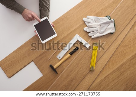 Carpenter's hands using a digital tablet and installing a wooden flooring with work tools all around, top view - stock photo
