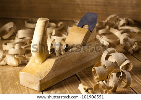 Carpenter's plane and shaving on a wooden planks - stock photo