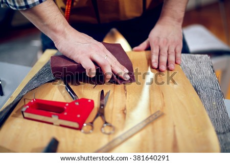 Carpenter sanding plank in his workshop - stock photo