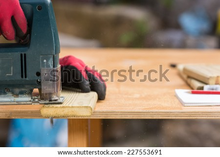 Carpenter sawing a board with a jig machine - stock photo