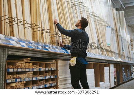 Carpenter selecting lengths of cut wood of a rack in a hardware store , low angle rear view from the side - stock photo
