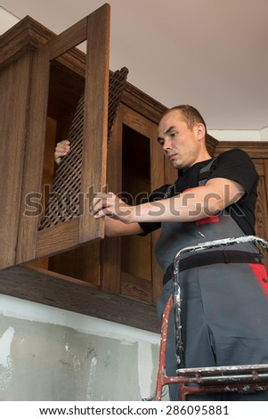Carpenter sets the grate in the door hanging cupboard. - stock photo