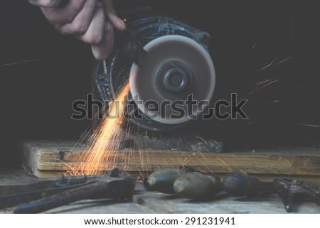 Carpenter sharpening old tool - stock photo