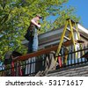 carpenter shingling a roof on a house remodel - stock photo