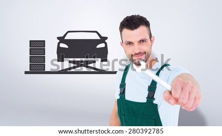 Carpenter showing wrench against grey vignette - stock photo