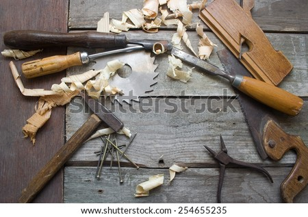 Carpenter table upper view. Old rusty and dirty carpenter`s hand tools lying on wooden table with sawdust. - stock photo
