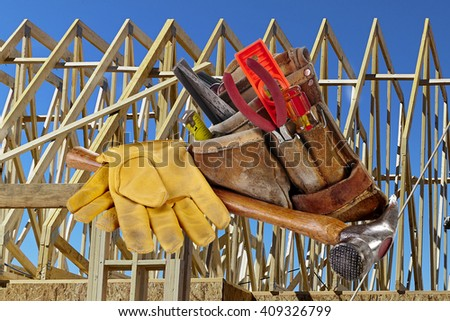 Carpenter tools, hammer, nails, screws, level, tape measure, screwdrivers, pliers and hacksaw with wood framed structure in background - stock photo