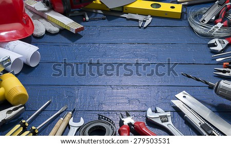 Carpenter Tools on Blue Wood. Blueprints are not subject to copyright. Words on them are regular like kitchen, bedroom, bathroom etc.  - stock photo