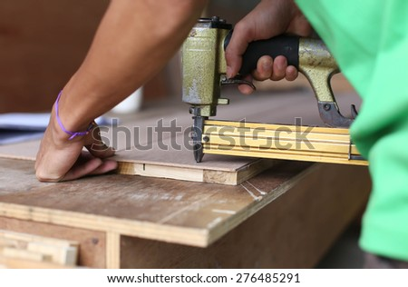 Carpenter used a nail gun on woodwork - stock photo