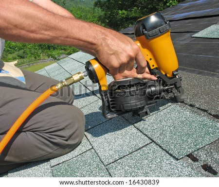 Carpenter uses nail gun to attach asphalt shingles to roof - stock photo
