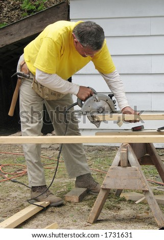 Carpenter using a circular saw - stock photo