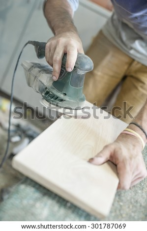 Carpenter Using Electric Sander. Carpenter sanding a wood with sander, outdoors - stock photo