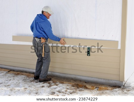 Carpenter using gauge to install fibrous cement siding - stock photo