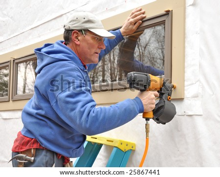 Carpenter using nail gun to install trim around windows - stock photo