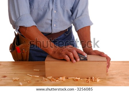 Carpenter wearing a toolbelt sanding a wooden box, isolated over white - stock photo
