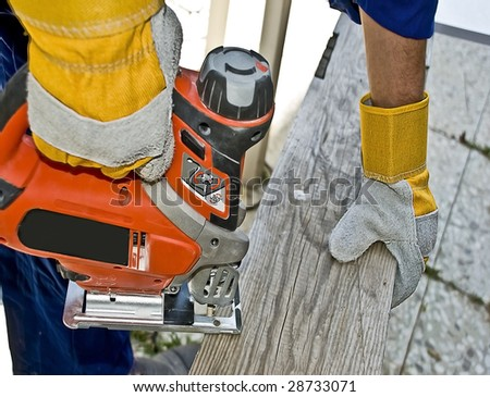 Carpenter with a fret saw cutting a board - stock photo