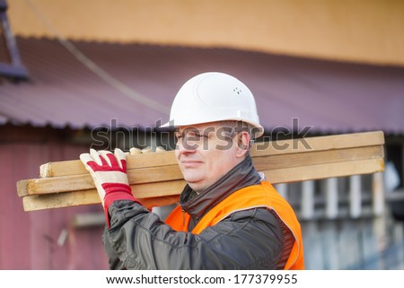 Carpenter with boards on their shoulders - stock photo