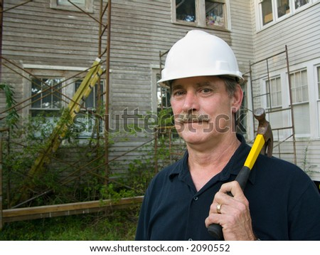 carpenter with hammer prepares to make repairs on house - stock photo