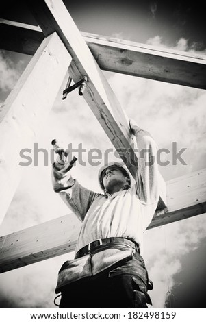 carpenter with hammer working on timber construction. Monochrome - stock photo