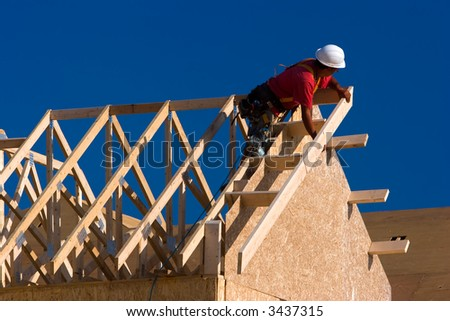 Carpenter with red shirt and white hardhat building a roof of a house at a construction site. - stock photo