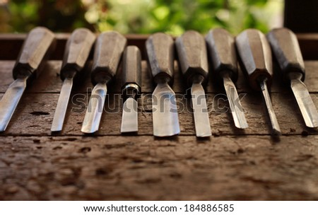 Carpenter wood chisel tool with loose shavings on old weathered wooden workbench - stock photo