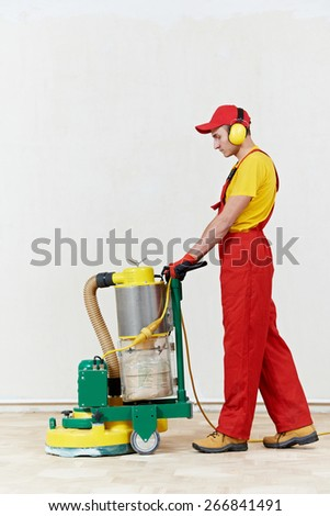carpenter worker polishing wood parquet floor during maintenance work by grinding machine - stock photo
