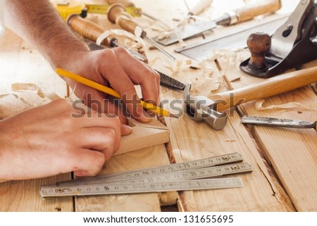 carpenter working,hammer,meter and screw-driver on construction background - stock photo