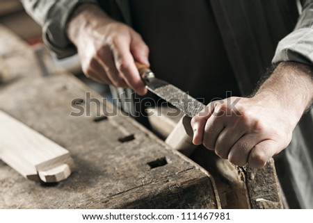 Carpenter working on a piece of wood with a file