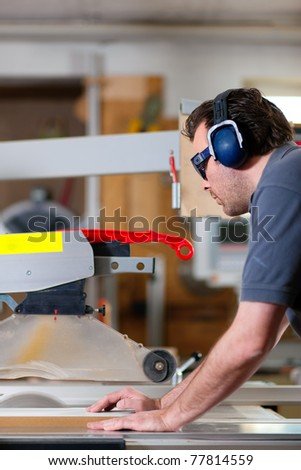 Carpenter working on an electric buzz saw cutting some boards, he is wearing safety glasses and hearing protection to make things safe