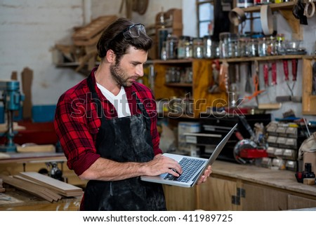 Carpenter working on his computer on his workshop - stock photo