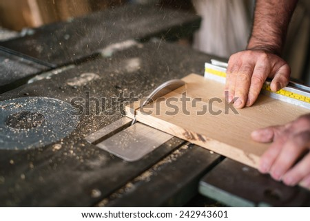 Carpenter working on the circular saw - stock photo