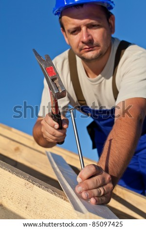 Carpenter working on the roof driving a nail in - shallow depth