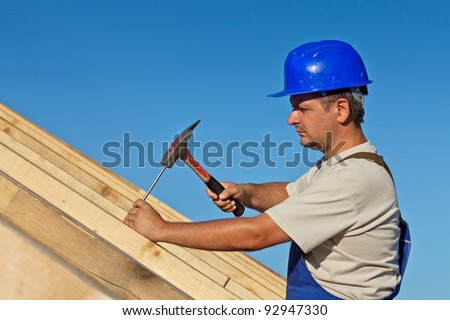 Carpenter working on the roof wooden structure - driving in big nail - stock photo