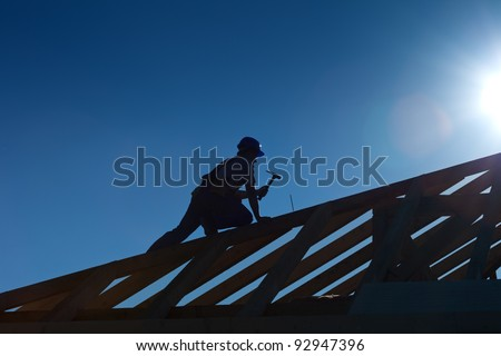 Carpenter working on top of the roof wooden structure - strong back light silhouette - stock photo