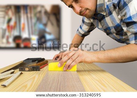 carpenter working the wood with sand paper tool at the workplace - stock photo