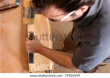 Carpenter working with a chisel and hammer in his workshop