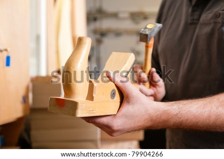 Carpenter working with a planer in his workshop, close up on the tool with hands