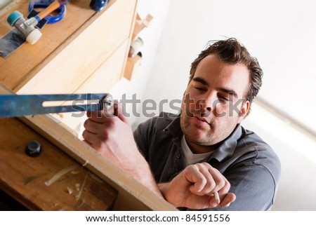 Carpenter working with angle and pencil in his workshop