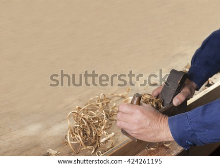 carpenter working with plane on wooden background.copy space - stock photo