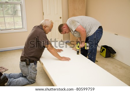 Carpenters using old door for pattern to cut out new interior doors,home will be sold on market - stock photo