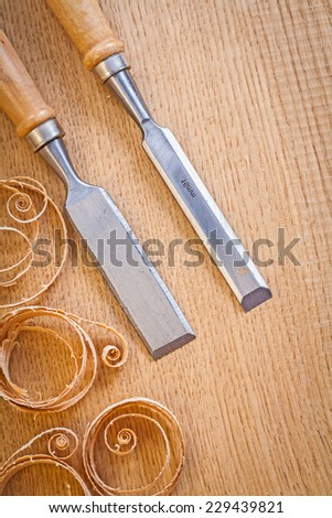 carpentery chisels on wooden board with wooden shavings - stock photo