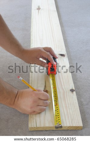 Carpentry, mans hand using tape measure to measure wood plank and marking it with pencil - stock photo