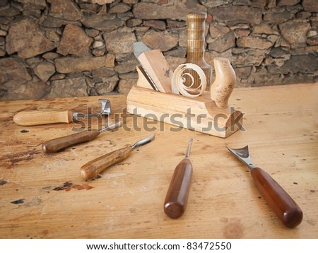 Carpentry tools spread on wooden table with stone wall in the background. - stock photo