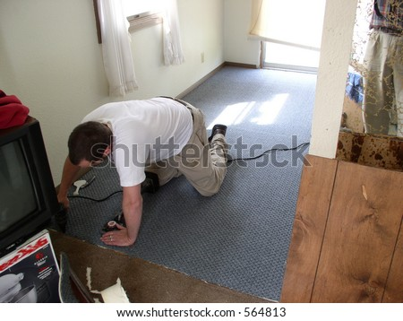 Carpet installer tacks down new carpet in a home - stock photo