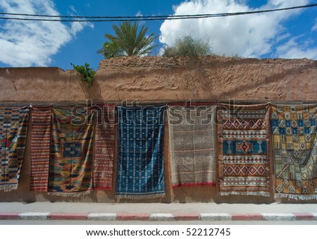 Carpets for sale hanging on a wall along the road near Fes in Morocco - stock photo