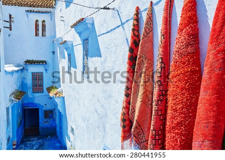 Carpets for sale on a street in Chefchaouen, Morocco, small town in northwest Morocco known for its blue buildings - stock photo
