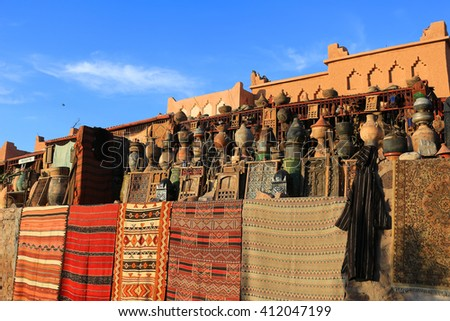 Carpets, vases, tajines and other pottery for sale in southern Morocco - stock photo