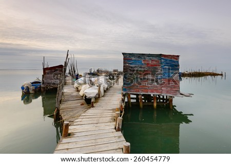 Carrasqueira, Alentejo, Portugal. Artisanal fishing pier with wooden stakes, is one of the largest in the world. Located in the Sado Estuary is an amazing tourist attraction. Landscape at Sunset.  - stock photo