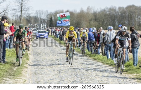 CARREFOUR de l'ARBRE,FRANCE- APR 12: Group of cyclists riding on the famous cobblestone road from Carrefour de l'Arbre during the Paris Roubaix race 2015. - stock photo